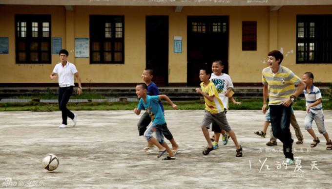 <p> Nichkhun (áo kẻ ngang) hào hứng chơi đá bóng với các em nhỏ trong một cảnh quay.</p>