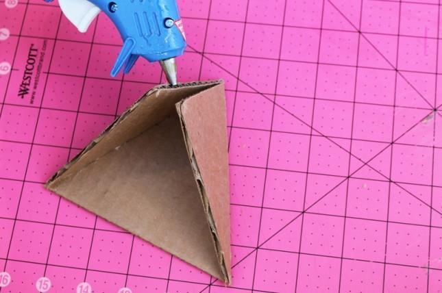"""<p style=""""text-align:center;""""> <strong>Bước 4:</strong></p> <p style=""""text-align:center;""""> Dán 2 hình của tam giác cạnh nhỏ vào mặt tam giác đáy to.</p>"""
