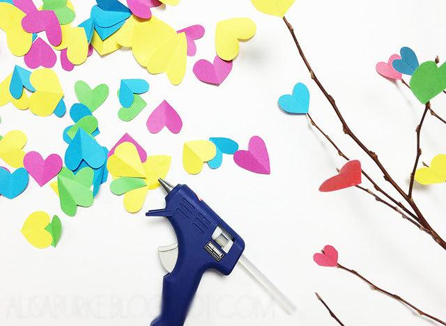 """<div style=""""text-align: center;""""> <strong>Bước 2:</strong><br /> <br /> Sau đó, bạn dùng súng bắn keo dán các hình trái tim rải khắp các cành cây khô trông cho tự nhiên. Không nên dán quá nhiều sẽ làm rối mắt nha các ấy.</div>"""