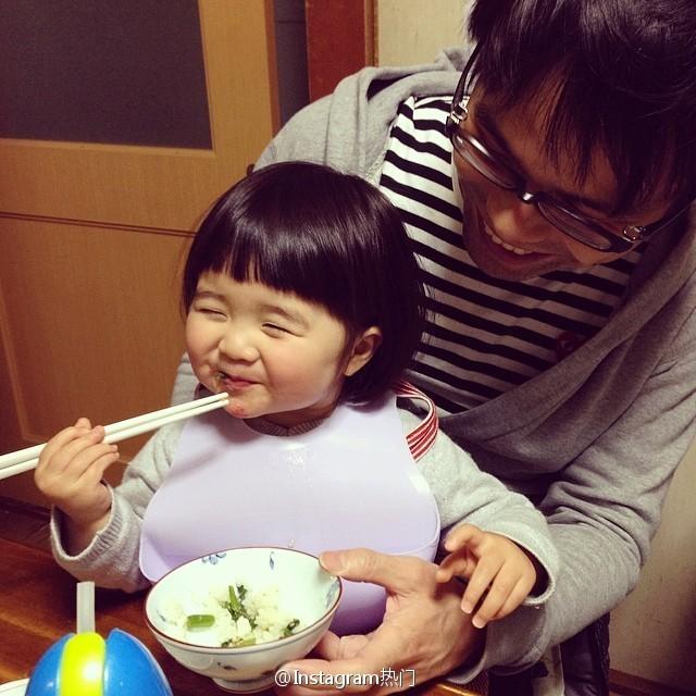 <p> Cô nhóc tít mắt sung sướng ngồi ăn trong lòng bố.</p>