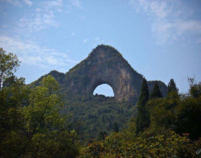 """<p class=""""Normal""""> 10. Moon Hill (Nguyệt Lượng Sơn), ở huyện Dương Sóc (Quảng Tây, Trung Quốc), là một ngọn đồi có vòm tự nhiên tạo nên từ một lỗ rỗng hình bán nguyệt xuyên qua đồi.</p>"""