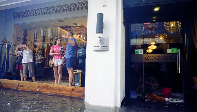 """<p> Du khách bị cầm chân vì phố ngập. Các tòa nhà trong phố cổ hoặc đã được lắp """"tường gỗ"""" chống tràn, hoặc phải dùng khăn chèn khe cửa cho nước khỏi lọt.</p>"""