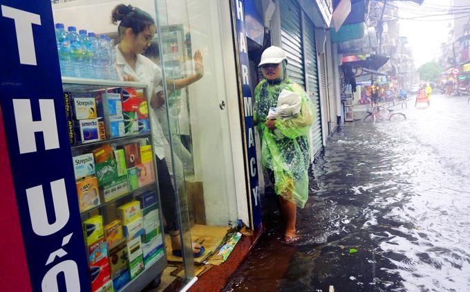 <p> Các khu phố ngập sâu được cắm biển báo. Người dân đi bộ men theo bậc tam cấp trên vỉa hè.</p>