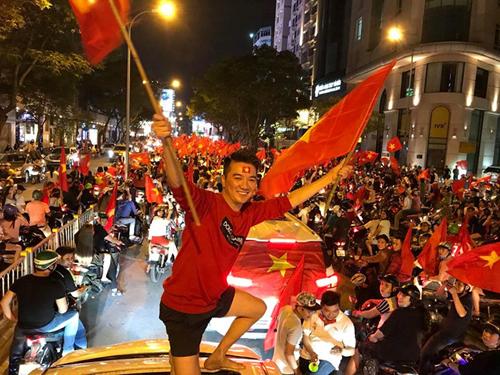 Đàm Vĩnh Hưng đứng trên xe hơi cầm cờ cổ vũ đội tuyển U23 Việt Nam sau chiến thắng tại trận bán kết.