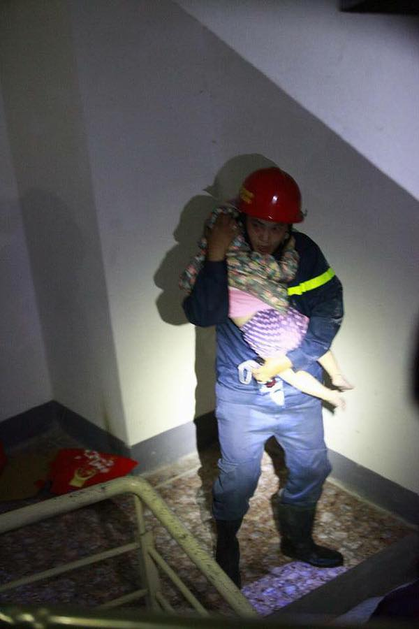 Người lính cứu hỏa này ôm chặt cháu bé trong tay mình, cố gắng đưa bé ra khỏi đám cháy.