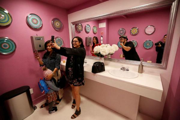 Du khách thích thú selfie trong không giannhà vệ sinh với chiếc gương 2 chiều.