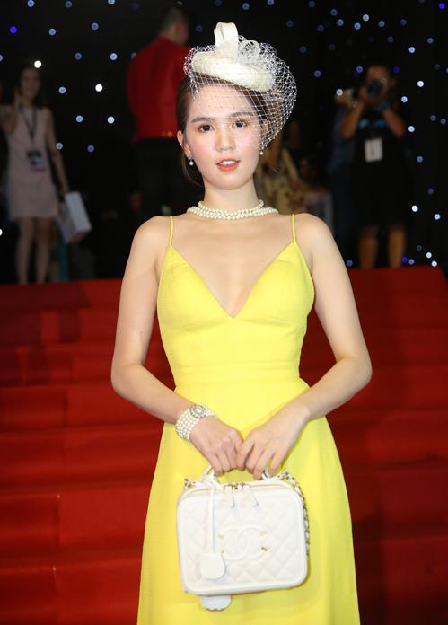 Ngọc Trinh vẫn trung thành với những chiếc váy hai dây tôn vòng một tối đa. Cô mix với mũ lưới và túi xách Chanel theo phong cách quý tộc.