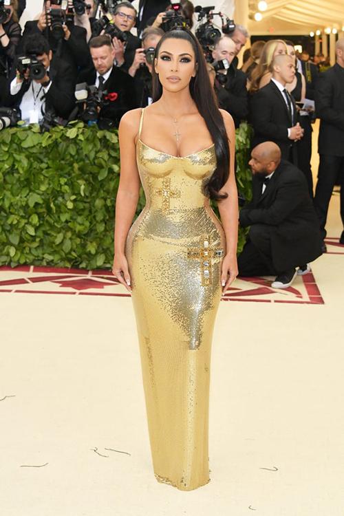Tối 7/5 (giờ địa phương), Met Gala 2018 chính thức khai màn tại Bảo tàng Nghệ thuật Metropolitan, New York, Mỹ. Trên thảm đỏ sự kiện được mệnh danh là Oscar thời trang có sự quy tụ của hàng trăm ngôi sao trong những trang phục với dress code Công giáo. Khác với những lần xuất hiện trước, Kim Kardashian năm nay diện váy metallic đơn giản của Versace, tôn lên đường cong đồng hồ cát.