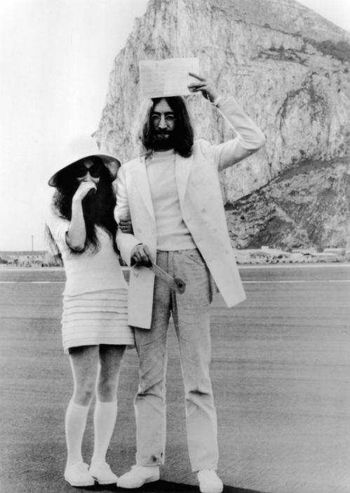 John Lennon khoe giấy chứng nhận kết hôn của họ trước dãy núi ở Gibraltar. John và Yoko kết hôn vào năm 1969 - 3 năm sau khi gặp nhau tại triển lãm của Yoko.