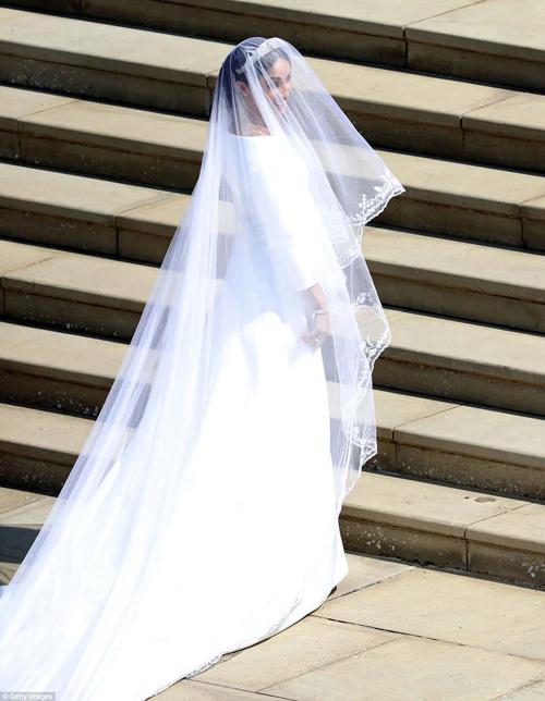 Váy của Meghan có phom dáng chữ A thanh lịch, đuôi không quá dài. Chi tiết cầu kỳ nhất là chiếc khăn voan trùm đầu dài 5 m, giúp bước đi của cô dâu duyên dáng hơn.