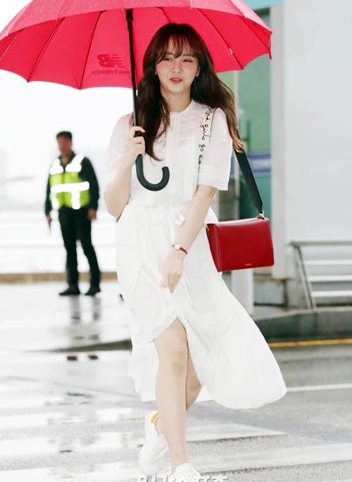 Kim So Hyun diện một bộ váy trắng, cầm ô đỏ ra sân bay, tạo hình ảnh đẹp như một bộ phim. Tuy nhiên, ngôi sao sinh năm 1999 gặp tình huống khó xử khi bị gió thổi tung váy, suýt xảy ra sự cố.