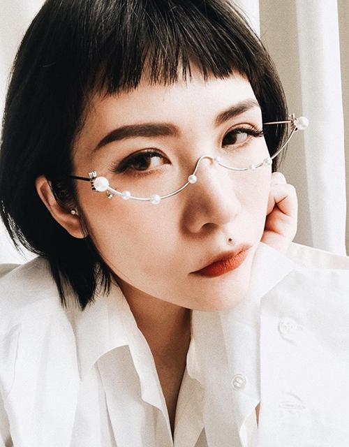 Beauty blogger Lâm Thúy Nhàn cũng chạy đua theo mốt gọng kính nửa vầng trăng, điểm xuyết hạt ngọc trai rất sang trọng.