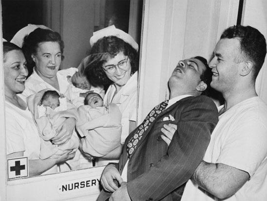 Hộ lý đưa những bé sơ sinh trong ca sinh ba đến với ông bố tại New York năm 1946.Ông bố sung sướng đến ngất đi.