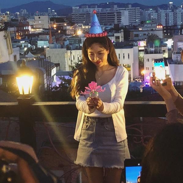 Hyun Ah cười e thẹn mừng sinh nhật sớm trên tầng thượng.