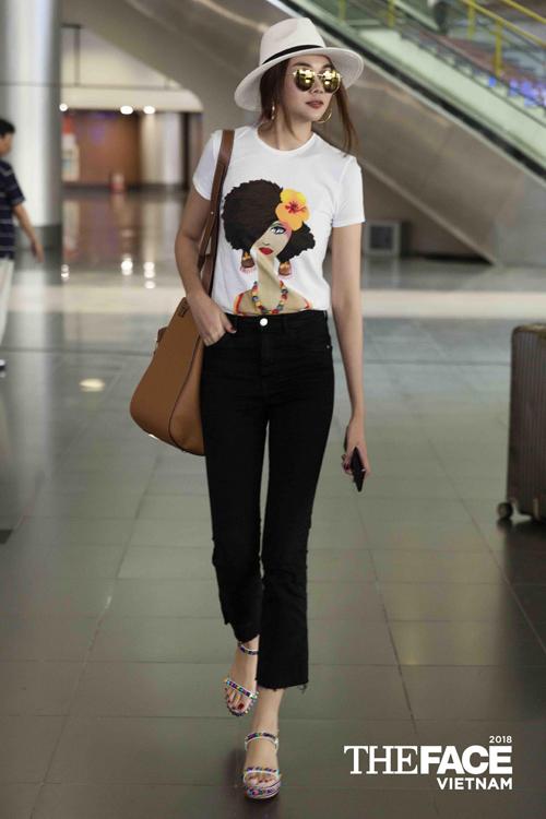 Không hẹn mà gặp, HLV Thanh Hằng cũng diện áo phông trắng in hình ra sân bay. Tuy nhiên cô trông đơn giản và năng động hơn khi mix với quần đen và sandals đế độn.