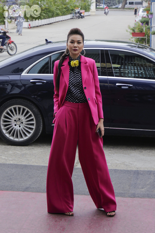Thanh Hằng nổi bần bật với cây hồng neon rực rỡ. Siêu mẫu còn kết hợp cùng hoa cài áo màu vàng trổ tài chơi màu sắc.