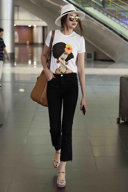 Áo thun trắng đơn giản được Thanh Hằng thổi vẻ sành điệu bằng những món phụ kiện như mũ panama, sandals đính đá màu sắc.