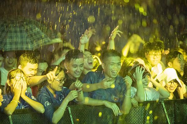 Trời mưa bắt đầu từ lúc 8h40 tối và kéo dài hơn 1 tiếng nhưng rất đông khán giả vẫn kiên trì chờ đợi những tiết mục của các nghệ sĩ. Các bạn fans được ban tổ chức hướng dẫn di chuyển vào bên trong sảnh để trú mưa. Và đây là một trong những tình huống khiến dàn nghệ sĩ vô cùng xúc động. Thay vì bỏ về, hàng trăm khan giả trong đó có những em bé đều nán lại trước phòng chờ của nghệ sĩ để được nghe họ hát.