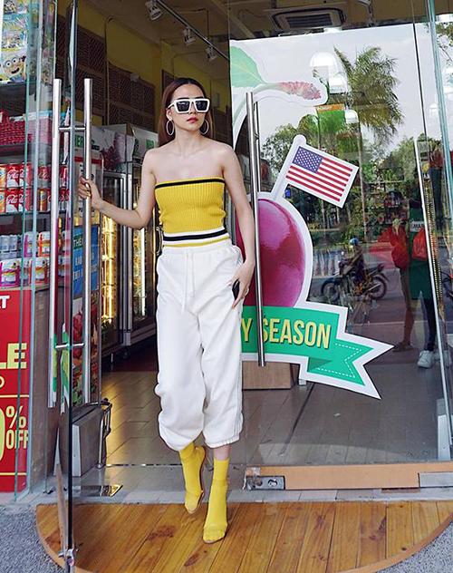 Thiều Bảo Trang chứng minh gu thẩm mỹ bằng cách phối đồ táo bạo. Để mix cùng áo vàng chanh, nữ ca sĩ diện tất cổ cao với sandals trong suốt, tạo nên một đôi boots chất chơi đồng điệu.