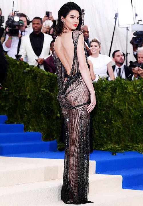 Bộ váy của Ngọc Trinh khiến nhiều người liên tưởng đến trang phục siêu gợi cảm Kendall Jenner từng mặc dự Met Gala 2018. Bộ váy có chung thiết kế xẻ tà, chất liệu lưới trong suốt mỏng manh tôn lên đường cong và vòng ba nảy nở,thân sau khoét rộng khoe lưng trần.