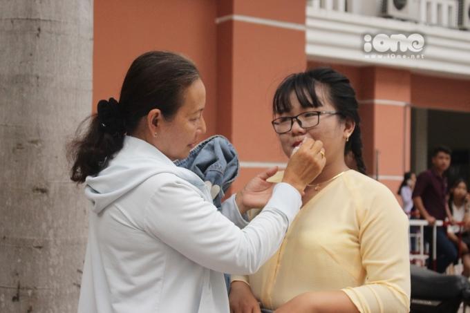 <p> Một người mẹ khác đang trang điểm cho con gái trước giờ thi.</p>