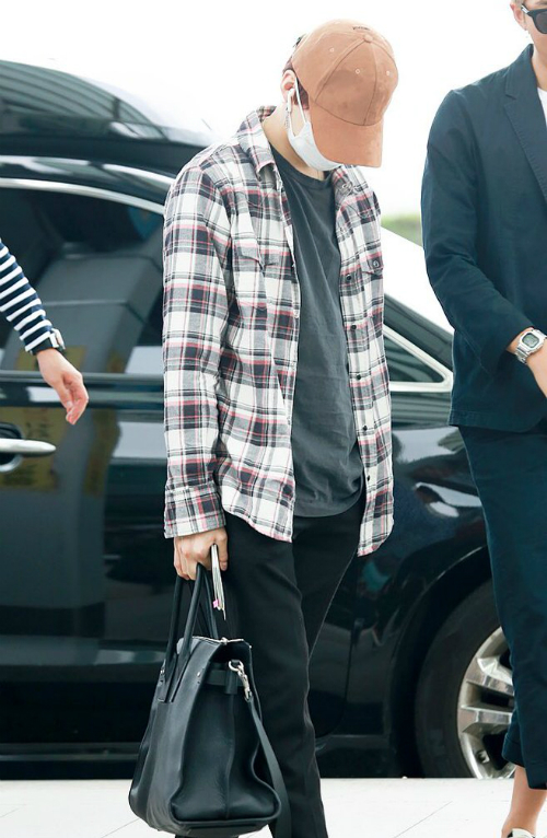 Suga luôn che mặt bẳng khấu trang và mũ khi ra sân bay.