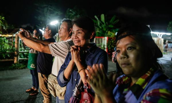 Những người dân cầu nguyện bên ngoài. Niềm vui hiện hữu trên gương mặt người phụ nữ này khi những đứa trẻ lần lượt được cứu thoát. Ảnh: Reuters