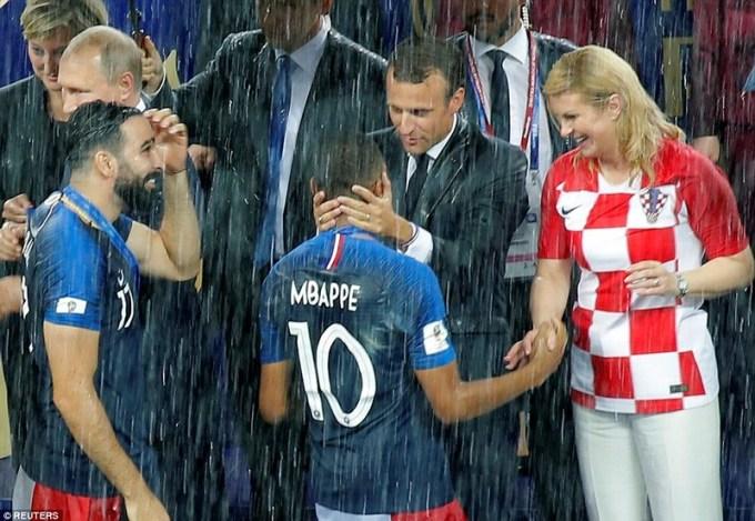 <p> Tổng thống Pháp ôm hôn Kylian Mbappe. Bên cạnh ông Macron là người đồng cấp của Croatia, Tổng thống Kolinda Grabar-Kitarovic đang nắm tay cầu thủ 19 tuổi. Ông Macron và bà Kolina đều ướt sũng vì mưa nhưng tỏ ra rất phấn khích vì trận cầu hay.</p>