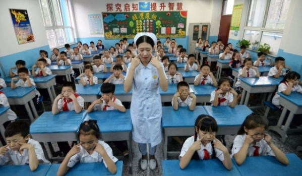 Một nữ y tá dạy học sinh tiểu học các bài tập về mắt, tại một trường tiểu học ở tỉnh Hà Bắc.
