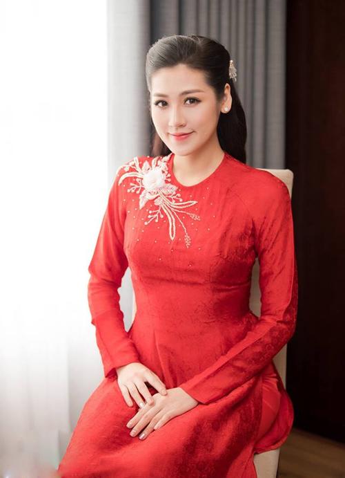 Trong lễ rước dâu, Á hậu khoe vẻ đẹp phúc hậu, nền nã trong tà áo dài đỏ rực, có kiểu dáng đơn giản, thiết kế cổ tròn cổ điển.