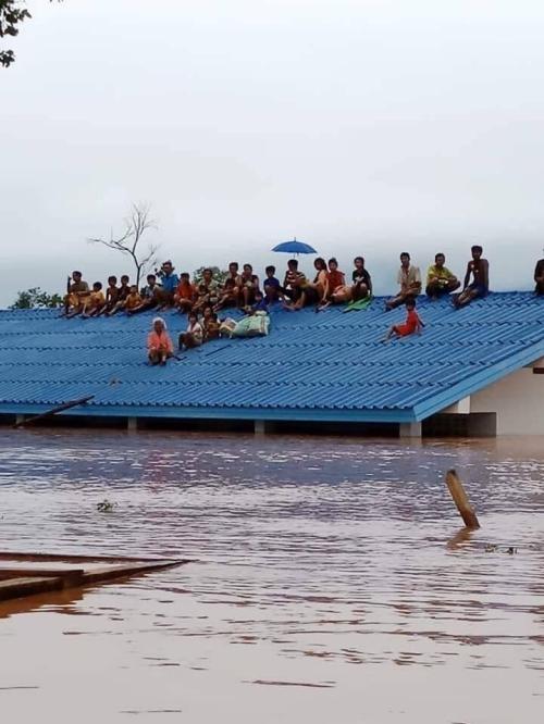 Cảnh tượng tan hoang, nhà cửa chìm trong biển nước đục ngầu. Người người trèo lêm mái nhà chờ cứu viện.