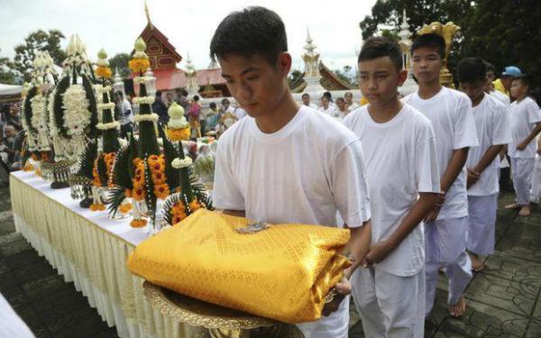 Huấn luyện viên bóng đá Ekkapol Chanthawong đi trước các học trò, họ mặc trăng phục trắng và cùng nhau thắp những ngọn nến vàng, chắp tay cúi lạy trước tượng Phật theo đúng nghi lễ của đất nước này. Ảnh: AP