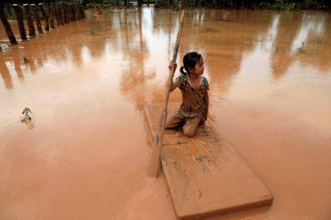 """<p> Cô bé lấm lem bùn đất chèo """"thuyền tự chế"""".</p>"""