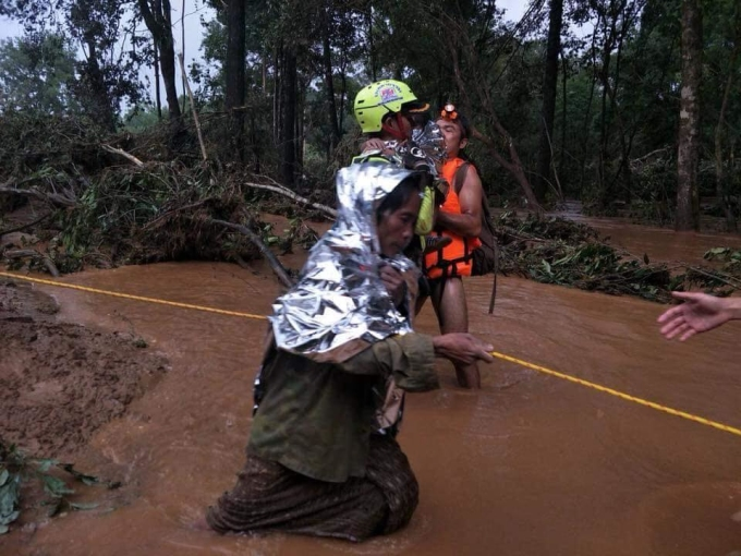"""<p> Tại các làng thuộc vùng """"rốn lũ"""" nước vẫn ngập quá đầu gối, đường đi đầy bùn nhơ nhớp. Đội cứu hộ phải chằng dây để người dân bám vào khi di chuyển.</p>"""