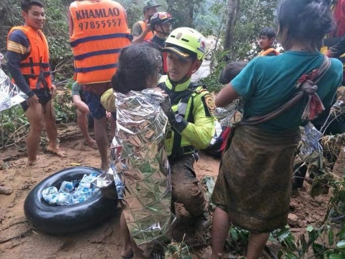 """<p> Một số trẻ nhỏ được cung cấp chăn bạc giữ ấm cho cơ thể. Theo Reuters, Phra Ajan Thanakorn, một nhà sư Phật giáo đang trở về từ Sannamxai cho hay vừa đưa 4 xe tải chở lương thực và thuốc men từ Vientiane đến, ông đang quay lại thủ đô để mang thêm hàng cứu trợ. """"Tình hình rất xấu. Mọi công tác cứu trợ đang tập trung vào Sannamxai. Tình nguyện viên ở đó đang phân phát thức ăn, thuốc uống cho những người sống sót. Họ vẫn đang thiếu lương thực, thuốc men và quan tài"""", ông nói.</p>"""
