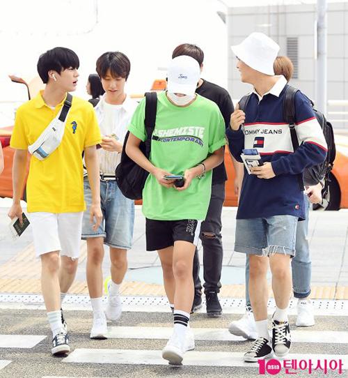 Các chàng trai của NCT rủ nhau mặc quần ngắn, áo phông màu sắc khi ra sân bay.