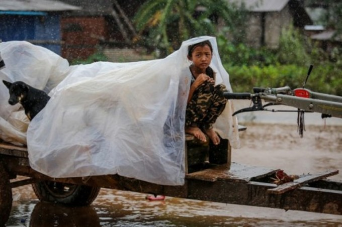 <p> Cô bé thu mình trên chiếc công nông, chỉ có tấm nilon để che mưa.</p>