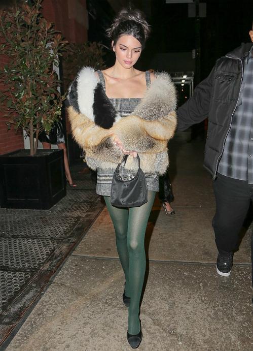 Kendall diện bộ cánh đi tiệc đậm chất vingate: áo khoác lông vũ, áo kẻ ca rô,tất da chân sáng màu và giày gót thấp màu đen cơ bản.