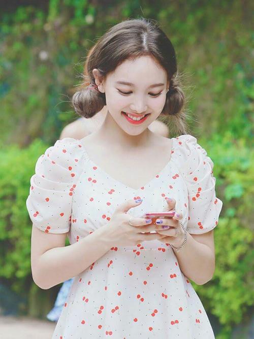Chiếc váy màu trắng, họa tiết cherry đỏ với phần tay bồng được Na Yeon diện rất tích cực khi ra phố. Trang phục tôn lên làn da trắng và vẻ đẹp trong trẻo của thành viên Twice.