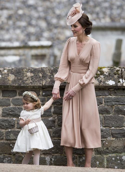 Tại đám cưới của Pippa Middleton, Kate mặc một chiếc váy dài màu hồng nude thanh lịch, cùng mũ hoa đội đầu tinh tế. Trong khi đó, tiểu công chúa đội vòng hoa, diện váy baby doll màu trắng với điểm nhấn là đai quấn cùng màu với váy của mẹ.