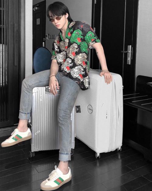 Sơn Tùng kết hợp áo sơ mi họa tiết nổi bật cùng quần jeans xắn gấu ôm sát và sneakers tiệp màu.