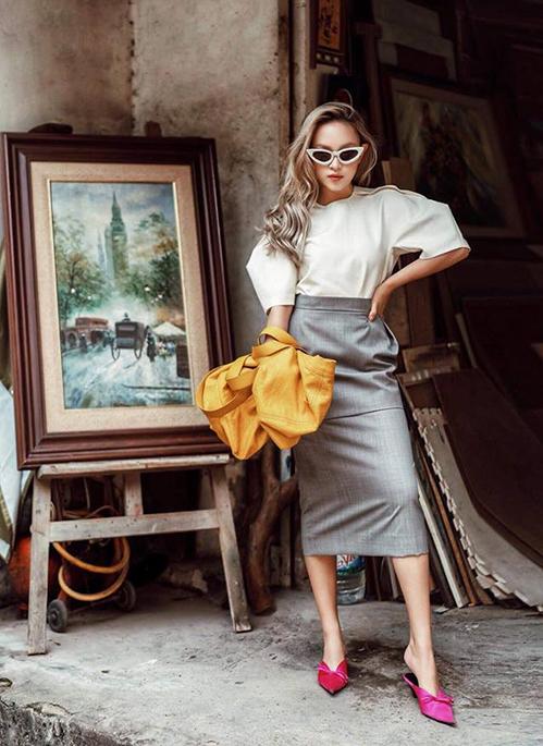 Diện áo tay bồng và chân váy bút chì đậm chất công sở, Châu Bùi chọn kính mắt mèo và đôi mules màu hồng rực giúp cả set đồ cá tính hơn hẳn.