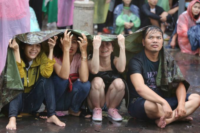 <p> Một số cổ động viên còn san sẻ với nhau mảnh áo mưa, che tạm cho đỡ ướt trong ngày hội bóng đá này.</p>