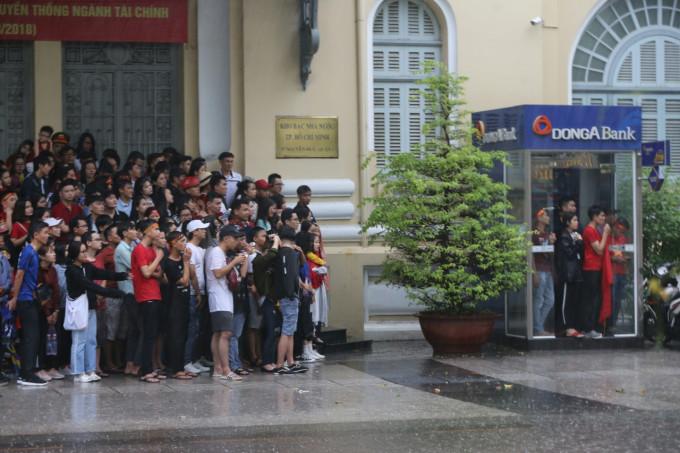 <p> Không có áo mưa, ô dù, nhiều bạn trẻ tụ thành một nhóm trú tạm dưới mái hiên của các tòa nhà cao tầng hoặc đứng chen chúc trong các điểm ATM rút tiền.</p>