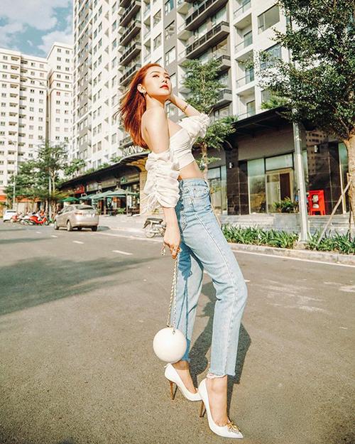Gây tranh cãi vềphong cách khi ngồi ghế nóng The Face nhưng ở đời thường, street style của Minh Hằng lại rất ấn tượng. Trong set đồ ra phố mới, cô diện một chiếc croptop trễ vai mix cùng quần jeans. Phụ kiện đi kèm làtúi xách Chanel, giày cao gót Versace tông xuyệt tông sắc trắng.