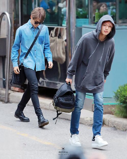 Jin xuất hiện thanh lịch với áo denim, quần skinny còn em út Jung Kook chuộng áo hoodie, túi xách to bản khi đi làm.