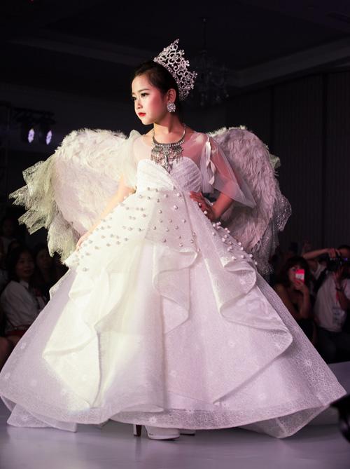 Đảm nhiệm vai trò trình diễn mở màn cho các bộ sưu tập là mẫu nhí Khánh Linh. Cô nhóc 6 tuổi khoác lên mình những bộ váy dạ hội nhiều chi tiết, đầu đội vương miện, chân đi giày cao gót 7 cm catwalk rất tự tin.