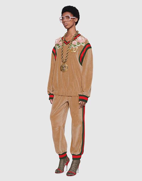 Thiết kế này có tên Gucci-Dapper Dan, gồm set áo nỉ và quần bo chun. Giá của chiếc áo là 3.700 USD, quần là 1.500 USD, tổng cộng Mai Phương Thúy phải chi 5.200 USD (hơn 120 triệu đồng) để sắm cả cây về. Theo Hoa hậu, cô có thể mặc bộ này đi ăn... cháo sườn và bún đậu.
