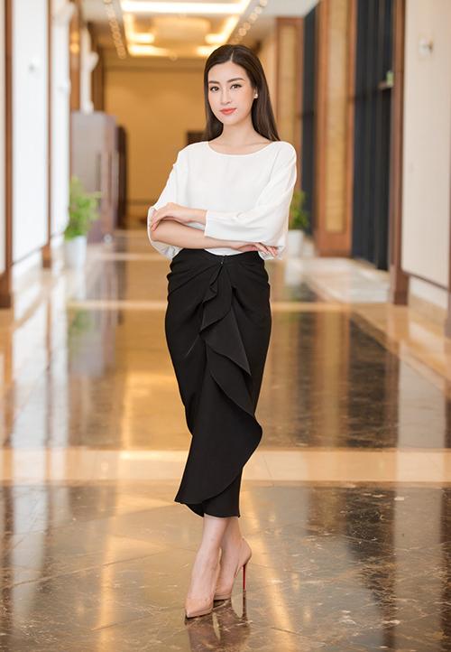Tuy là chân váy đen đơn giản nhưng chiếc váy lại được cách điệu với phần diềm bèo nhún lệch một bên, tăng thêm độ nữ tính và yêu kiều. Nối tiếp Hà Tăng, Đỗ Mỹ Linh cũng diện thiết kế này với cách phối tương tự.