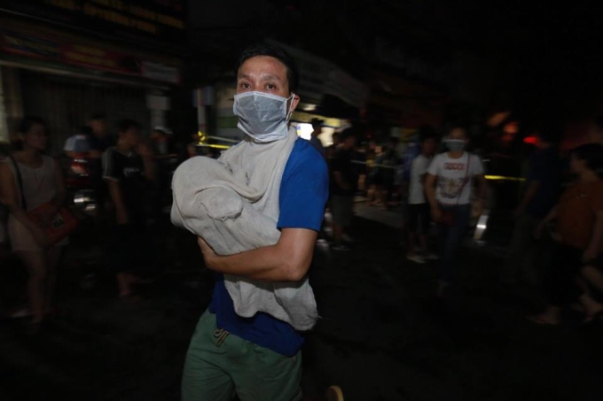 <p> Lo sợ lửa lan rộng, người dân đã khẩn trương sơ tán người và của. Trong ảnh, một người đàn ông trùm kín khăn, bế đứa con sơ sinh của mình ra khỏi khu vực cháy.</p>